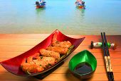 stock photo of deep  - traditional Vietnam deep fried shrimp and pork rolls in breadcrumbs served on a wood table top by the beach - JPG