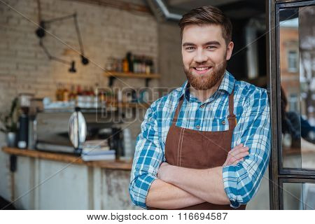 Happy attractive bearded barista standing with arms crossed in cafeteria