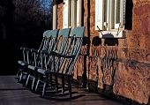 stock photo of farm-house  - a row of painted rocking chairs on the front porch of an old stone farm house - JPG