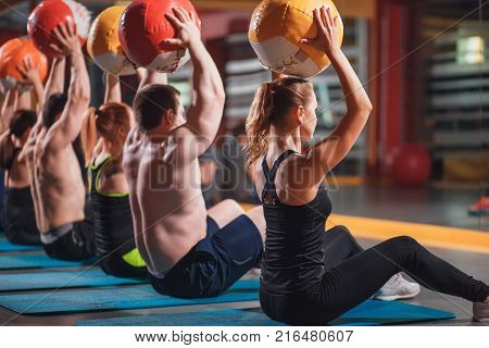 poster of cross fit athletes perform the exercise with the ball. cross fit and fitness. team spirit.