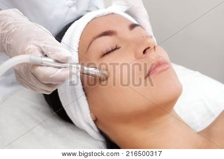 poster of The Cosmetologist Makes The Procedure Microdermabrasion Of The Facial Skin Of A Beautiful, Young Wom