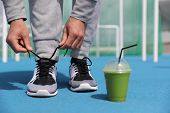 Gym fitness man getting ready tying running shoes with green smoothie detox beverage. Closeup of run poster