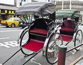 stock photo of rickshaw  - Two Rickshaw parked in urban traffic Japan - JPG
