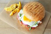 Tasty burger with bacon and egg on table poster