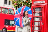 London tourist travel woman with UK flag umbrella, telephone box, red big bus. Europe travel destina poster