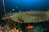 Ghost net. Old discarded fishing net causes environmental problem on coral reef poster