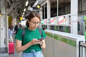Asian Girl Play Smartphone For Entertainment And Work Outside The Office Or Outside. Out Of Office C poster