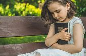 Reading The Holy Bible In Outdoors. Christian Girl Holds Bible In Her Hands Sitting On A Bench. Conc poster