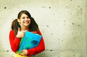 picture of bagpack  - young student with her book school having thum up - JPG