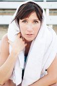 picture of bleachers  - Tired female athlete with towel sitting in the bleachers - JPG