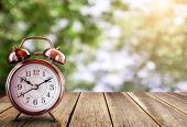 Retro Alarm Clock On A Wooden Table With Blured Bokeh Background. Save Time Savings Daylight Up Retr poster
