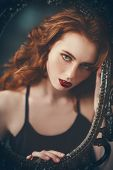 A portrait of a gorgeous beautiful young redhead woman looking through the frame of the mirror. Beau poster