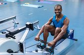 Portrait of African-american fit man exercising on rowing machine in fitness center. Bright modern g poster