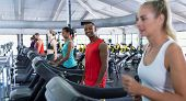 Portrait of African-american fit man exercising on treadmill in fitness center. Bright modern gym wi poster