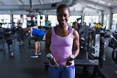 Portrait of African-american fit woman exercising with dumbbells in fitness center. Bright modern gy poster
