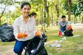 Young Asian Woman And Group Of Volunteers Wearing Orange Gloves And Collecting Garbage In Trash Bin  poster