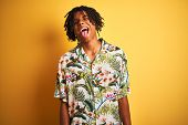Afro man with dreadlocks on vacation wearing summer shirt over isolated yellow background sticking t poster