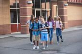 Large, diverse group of kids leaving school at the end of the day. School friends walking together a poster