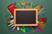 Blank blackboard with chalk and stationery accessories: pencils, pens, other office supplies on gree poster