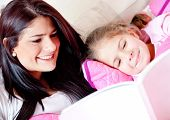 stock photo of girlie  - Cute girl reading a bedtime story with her mother - JPG