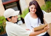 image of shipping receiving  - Woman receiving a package at home from a delivery guy - JPG