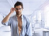 picture of tease  - Sexy hunk male model with open shirt in modern business setting with blue toning - JPG
