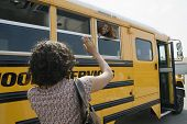 stock photo of bye  - Rear view of woman waving good bye to her daughter in school bus - JPG