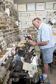 stock photo of locksmith  - Side view of senior locksmith working in store - JPG