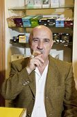 Portrait of middle-aged tobacco store owner smoking cigar