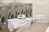 image of laundromat  - Ironing board with washing machines in Laundromat - JPG