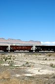 stock photo of boxcar  - Train boxcars set against a background of desert mesas and blue sky, and a foreground of sand and sagebrush.