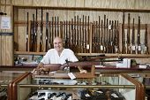 stock photo of gun shop  - Portrait of a happy weapon shop owner - JPG