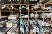 foto of ferrous metal  - series of different sizes metal pipes on shelf - JPG