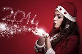 foto of blowing  - Beautiful brunette in the Santa costume blowing snowflakes and make New Year numbers 2014 - JPG