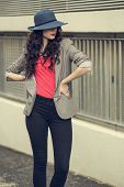 Attractive glamorous brunette wearing stylish clothes posing outside on a cloudy day