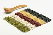 stock photo of tablespoon  - colorful striped rows of beans with wooden tablespoon - JPG