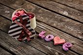 Open heart shaped Valentines Day gift box with heap of small hearts inside and word love on old wood