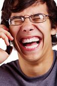 picture of laugh out loud  - Close up portrait of laughing young man in glasses talking by mobile phone over white background - JPG