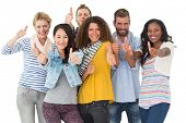 Happy group of young friends giving thumbs up to camera on white background