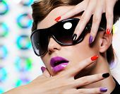 Woman with multicolored manicure and fashion stylish sunglasses