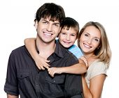 stock photo of pretty-boy  - Happy young family with pretty child posing on white background - JPG