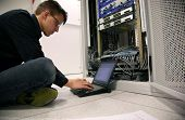 stock photo of cat5  - IT Engineer Configuring Network Devices - JPG
