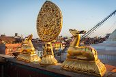 stock photo of dharma  - Buddhist golden deers and the wheel of the Dharma Boudhanath Kathmandu Nepal - JPG