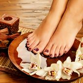 picture of pedicure  - Closeup photo of a female feet at spa salon on pedicure procedure - JPG