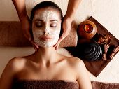 stock photo of mask  - Spa massage for young woman with facial mask on face  - JPG