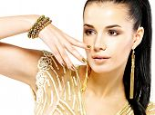 Pretty woman with golden nails and beautiful gold jewelry isolated on white background