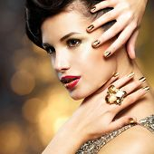 picture of brunete  - Beautiful fashion woman with golden nails and gold ring over style background - JPG