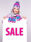 pic of outerwear  - Adult smiling  woman in winter outerwear  holds the white banner with sale word on it - JPG