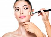 image of foundation  - Makeup artist applying liquid tonal foundation  on the face of the woman - JPG