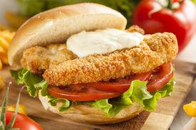 stock photo of tartar  - Breaded Fish Sandwich with Tartar Sauce and Fries - JPG